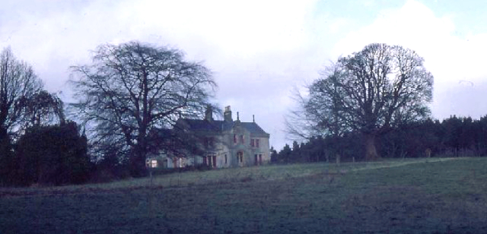 Shows a large manor on a hill obscured by trees.