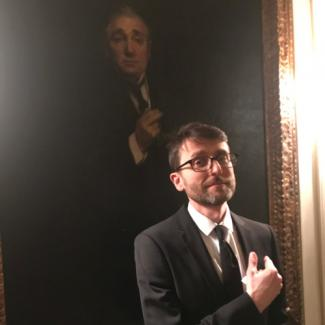 Man in suit standing in front of oil painting of man in suit