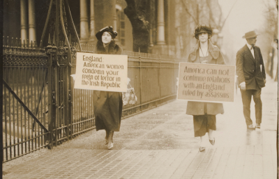 Two women holding signs in street.