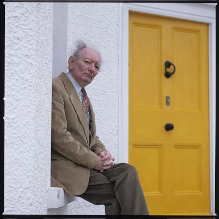 Older gentleman sitting beside a bright yellow door.