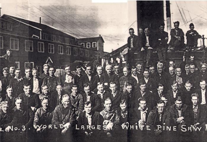 Group of workers standing in from of lumber yard in 1925. Solemn.