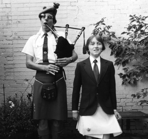 A lad of 12 or so years, wearing a blazer, tie, kilt, and smile is Irish dancing, arms at sides, floppy straight hair moving with his steps. He dances beside a man of 30 or so years wearing late 70's style shades, a short sleeved white shirt, tie, kilt, hat, and bag pipe. He is blowing on the blowpipe while squeezing the bag under his arm and playing the chanter with both hands. They are outside in front of a brick wall.