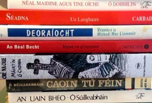 Stack of books with spines showing book titles in the Irish language.