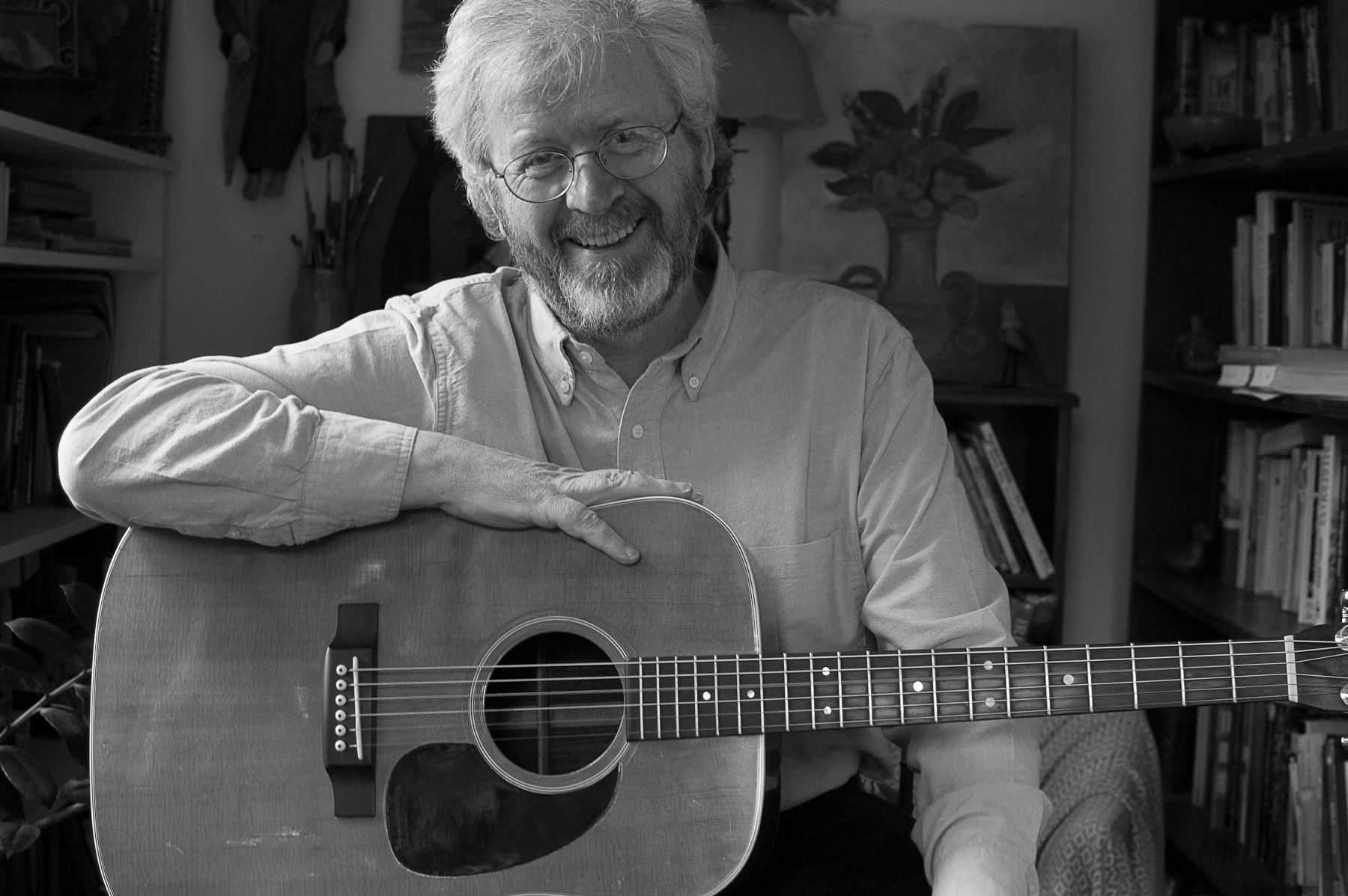 Joyful older man sitting at ease holding his guitar and smiling right at the camera.