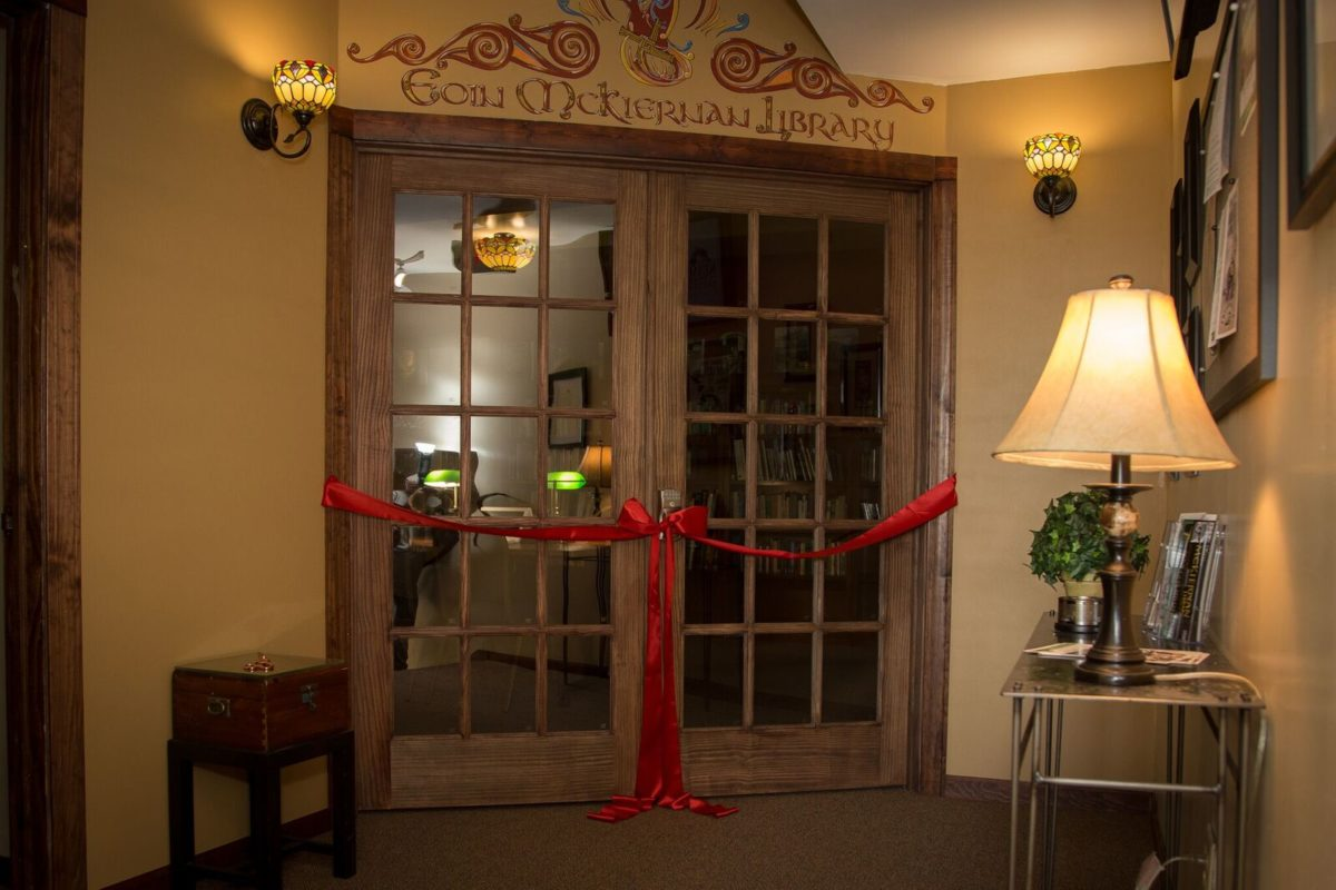 Long, heavy red velvet red ribbon is draped in front of wooden French doors, tied off in an extravagant bow to dissuade the curious. It's an inviting entrance surrounded by a painted ornaments name above and tiffany style lamps on either side.