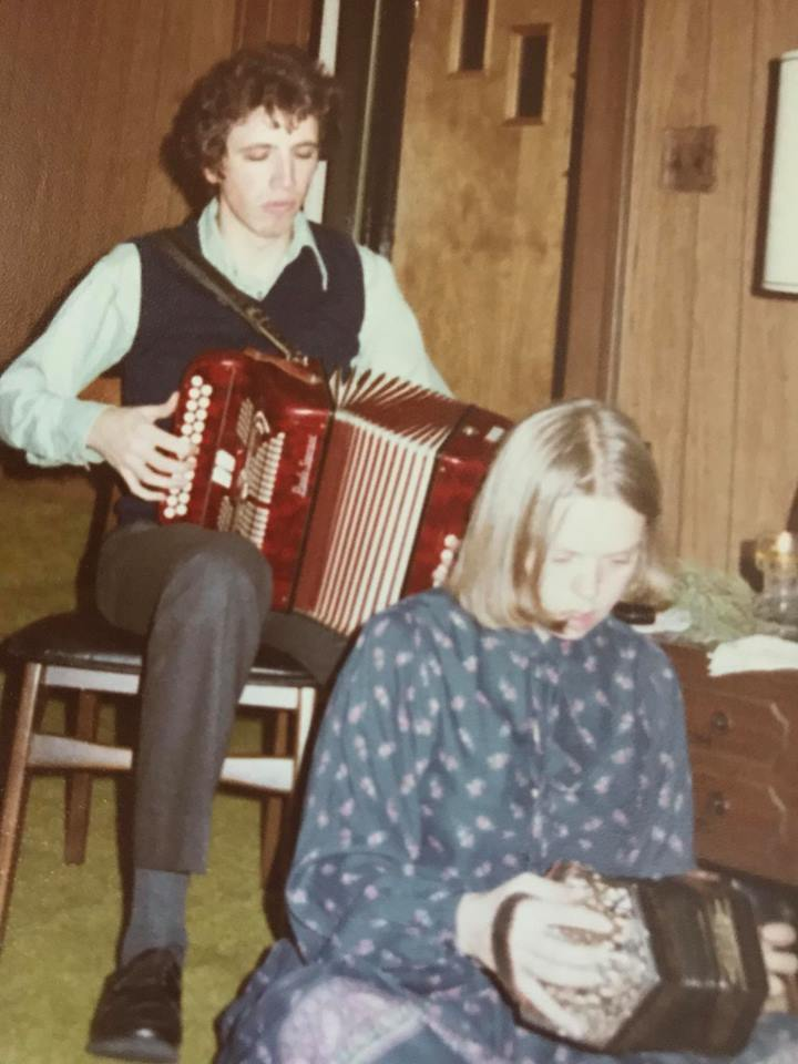 Young man seated on a chair playing box. A young woman sits on the floor in front of him playing concertina.