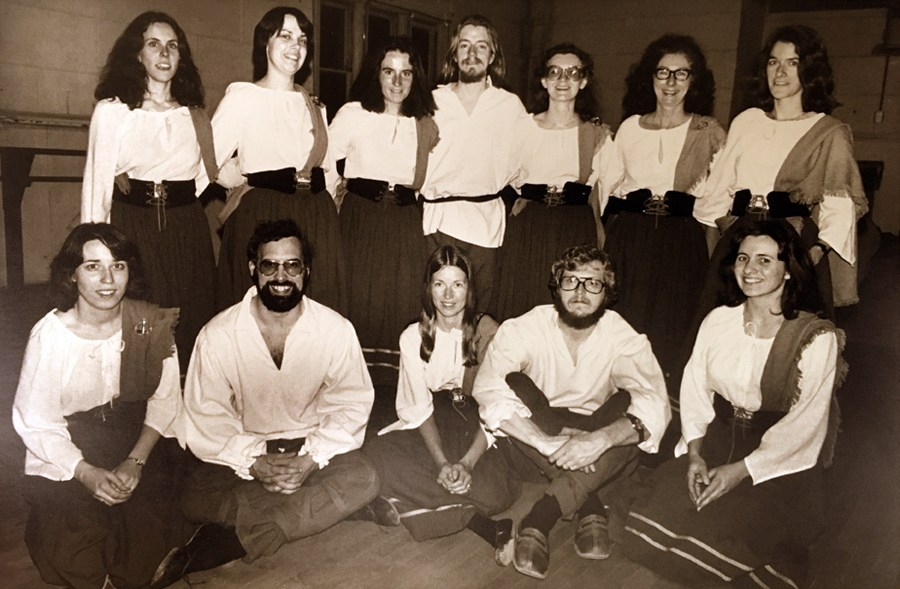 Two rows of six dancers pose for a picture in white tops, the first row sit on the floor, the second stands behind them. They look happy, healthy, and full of energy.