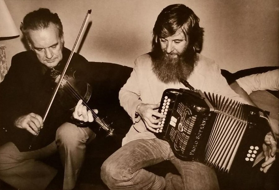 Older clean-cut gentleman wearing slacks and blazer plays fiddle next to a wildly bearded young box player in tight jeans. They appear to be sitting on a couch with lamps next to them.