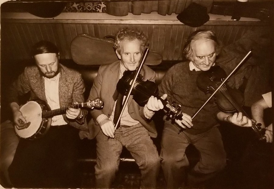 Three older gentlemen, each with some interesting hairstyles and more interesting faces, sit on a wooden bench, one is playing a banjo, the other two play fiddles. They have the air about them of knowing what they're about and being supremely happy in their time and circumstance.