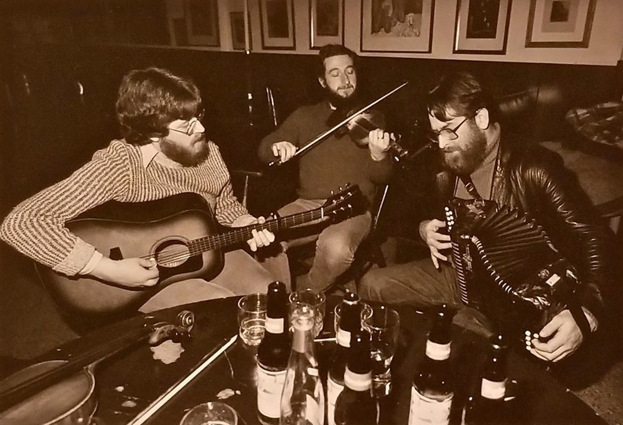 A table strewn with beer bottles and glasses is surrounded by three musicians, all men, all bearded. We see a guitar player, a fiddle player, and a box player. They appear to have been in those spots for quite some time, and it looks as though they have no intention of leaving any time soon.