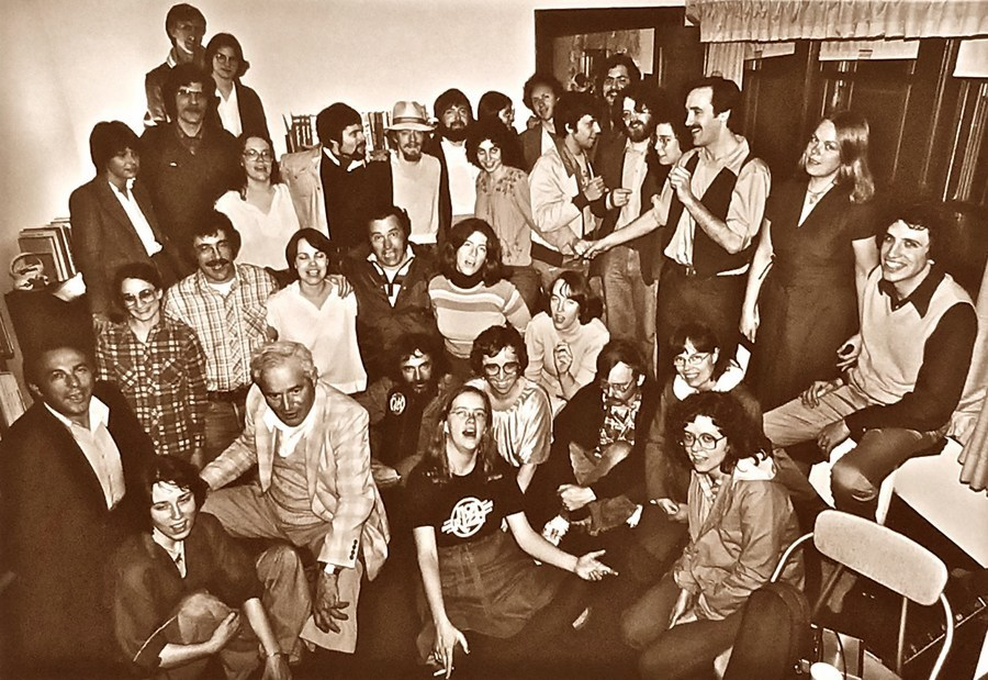 PC Dave Aronow. Circa 1980. Sepia photo of 25 or so young people crammed into a living room mugging for the camera.