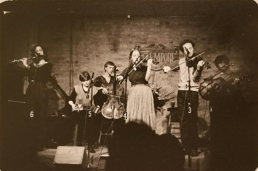 Concertina, cello, guitar, flute, and fiddles are the instruments being played by this six piece band.
