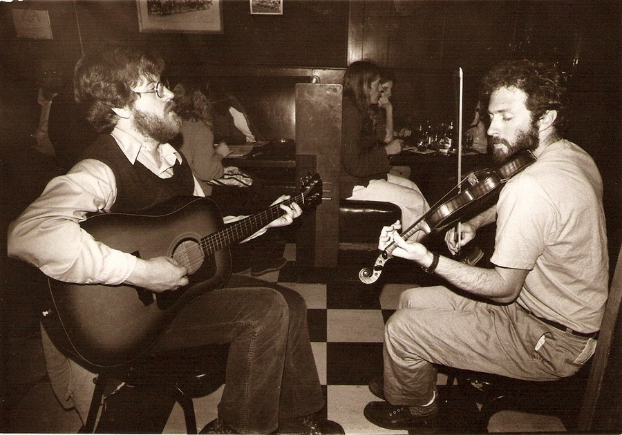 Two bearded men sit facing each other on cheap chairs sat on a black and white tiled floor. The men are playing music, one a guitar, the other a fiddle. Both appear to be completely engrossed in what they are doing and hearing, both listening intently with eyes closed.