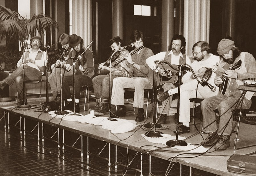 A long row of musicians sit side by side on what looks to be a temporary stage, each play different Irish instruments.