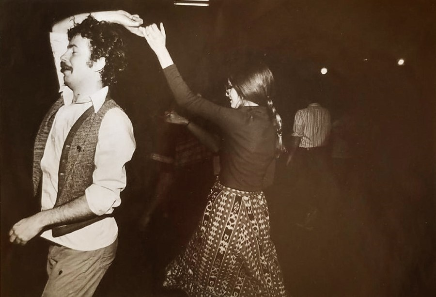 Man, eyes closed in state of dance bliss, hand extended to hold the hand of the young lady he is turning round himself.