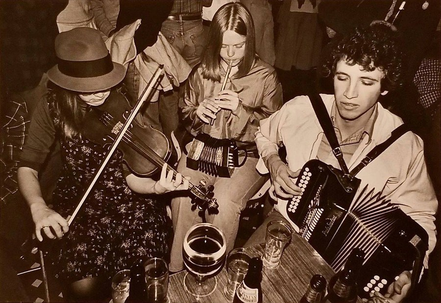 A trio of traddies playing music around a short table where a multiplicity of beverages sit. Handsome box player sits with eyes closed, long straight haired woman plays whistle with a concertina in her lap, and the female fiddler plays while wearing a face obscuring hat.