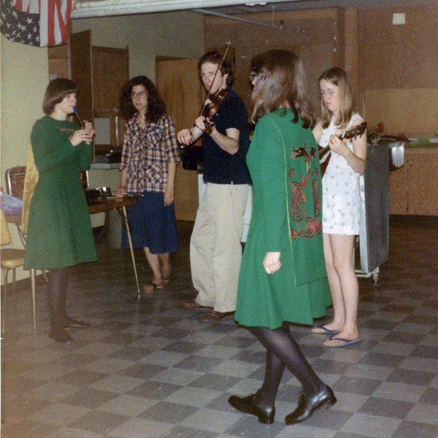 Green dressed gals standing standing in what looks to be a kitchen with a checkered floor.