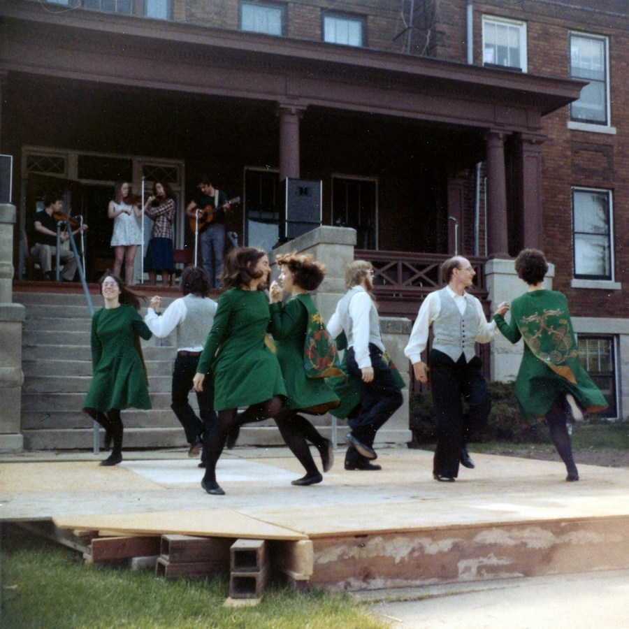 Green dresses fly on the lasses and the men swing in black bottoms and white shirts. They are in the middle of a ceili formation in front of a large brown house with a band playing on the huge front porch.