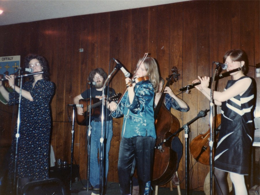 Long haired female fiddler in shiny shirt plays on stage next to a funky black and white dress wearing flute player sporting a gamine short haircut. Other band members include upright bass, bearded guitarist, and a second female flute player. Guys in the back, gals up front.