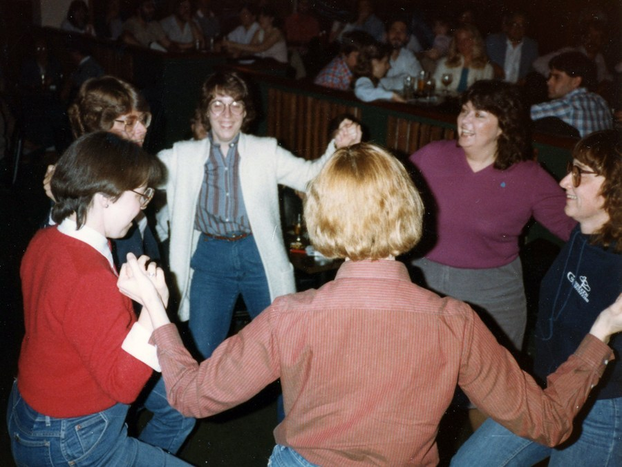 Circle of women facing inward, grasping hands and clearly dancing. Women are smiling. Clothing is late 70s/early 80s.