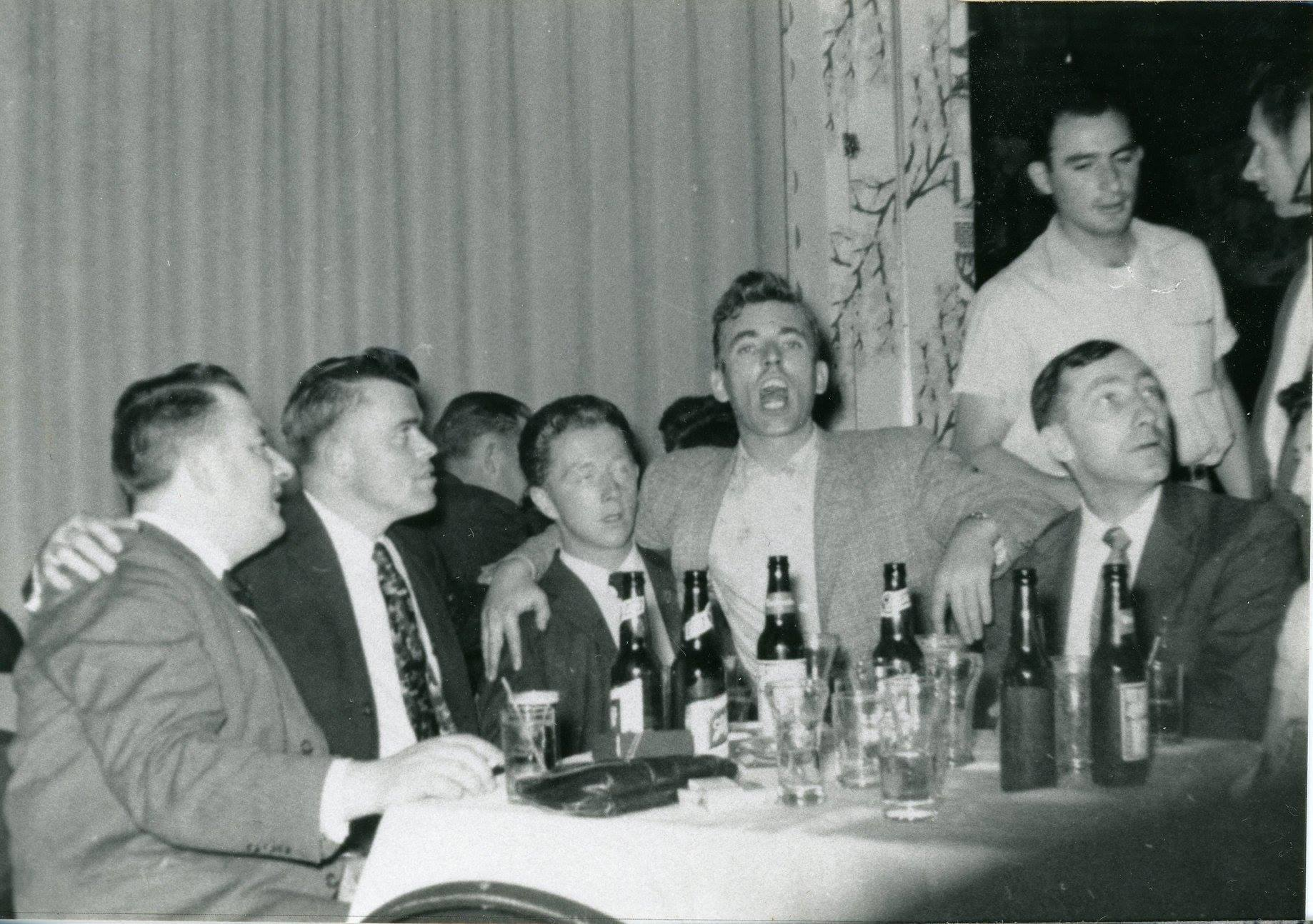 One man gestures widely at the photographer while seated at a table with four other men.