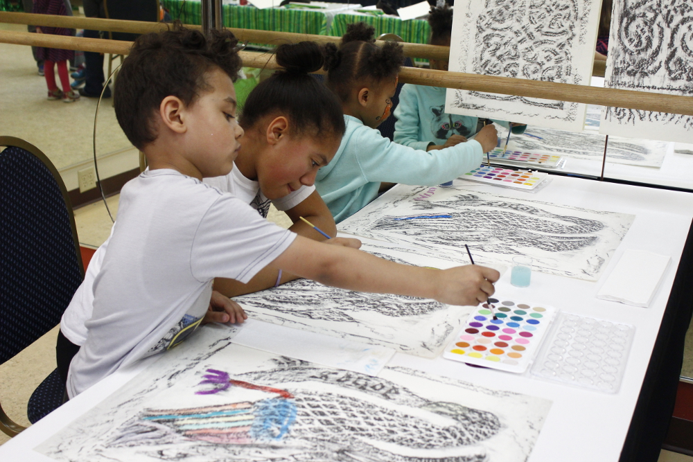 Children coloring knotwork at a table during an outreach event.
