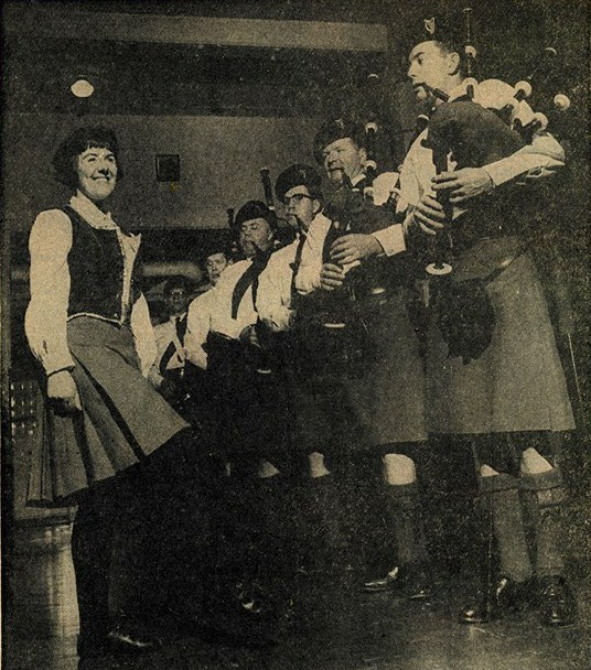 All eyes are on the smiling dancer as she steps to the line of Highland pipers playing right in front of her. All are in uniform and look quite impressive.