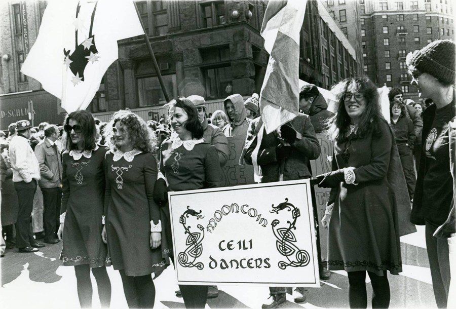 Photo of women in matching costumes carrying a large Mooncoin sign, crowds are behind them and include people holding an Irish flag.