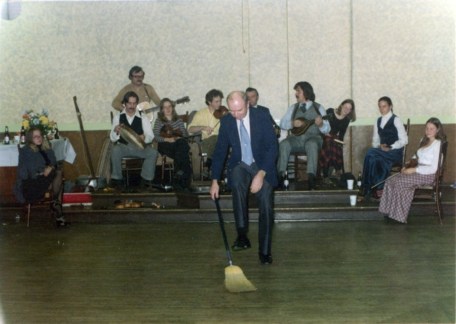 A lone, spritely man with little hair  stands in the middle of a large dance floor, band behind him. In his hand is a broom and he appears to be lifting one leg over the handle. A broom dance, you say? Yes, you'd be correct.