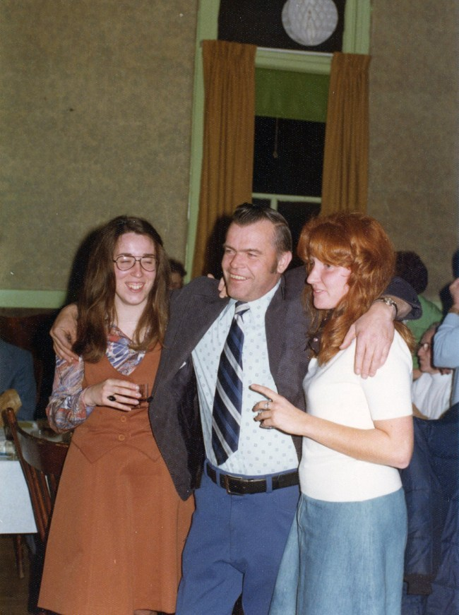 Snazzy clean shaven man wearing a tie and suit jacket has his arms draped confidently around two gals who are at ease and laughing. They appear to be at a big event and are having a fabulous time.