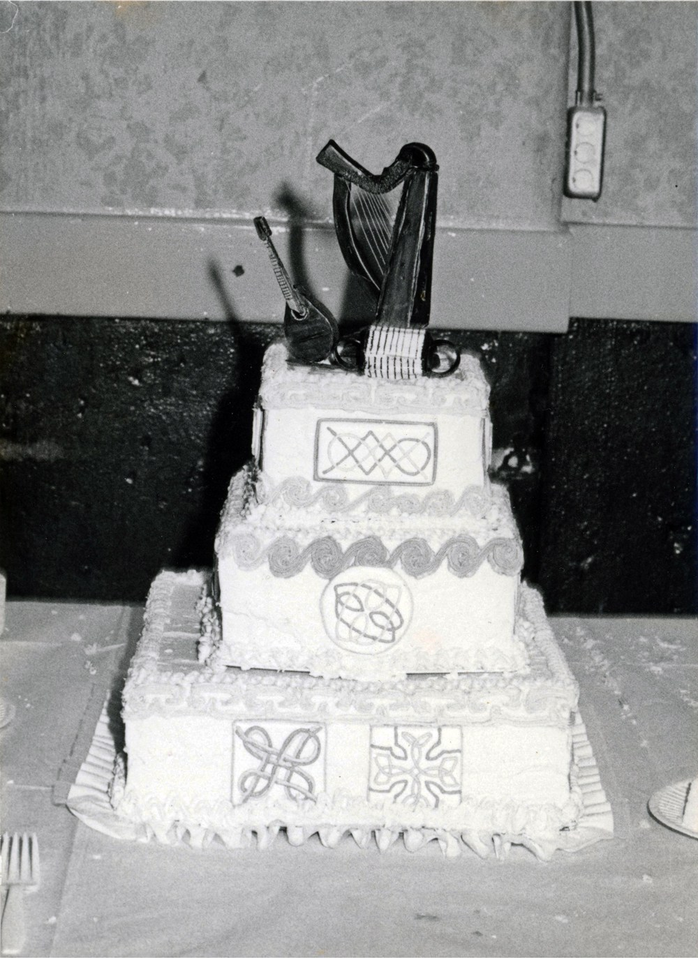 Glorious white wedding cake with knotwork decorating the sides, obviously hand done with love. On top sits a harp!