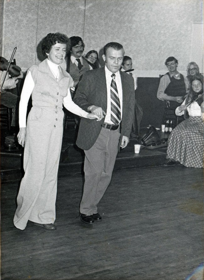 Who is svelte young woman who can pull off a pantsuit like nobodys  business? A dark haired woman and jacket wearing man stand side by side, hands embraced, caught just at the moment they are going to step forward on the dance floor. Their weight is forward, their faces bright with anticipation of the dance.