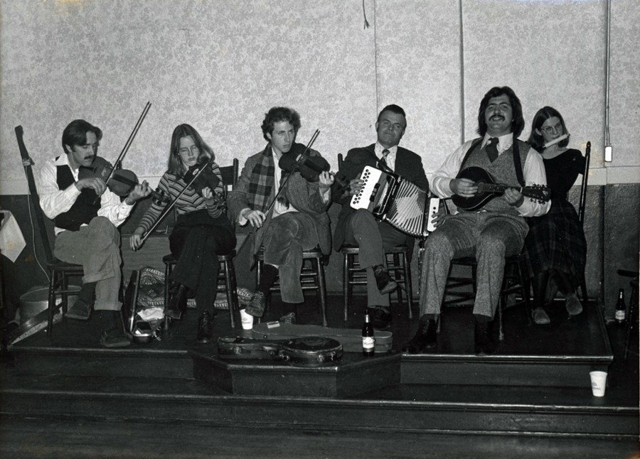 A largish band in fancy clothes sitting comfily on a set of beachers whilst playing their accordion, mandolin, fiddle, whistle and more!