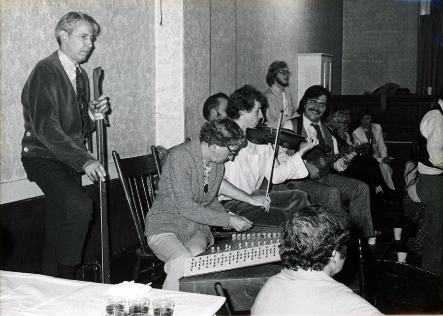 Someone playing a hammer dulcimer while a singer waits behind at a mic for his chance to sing.