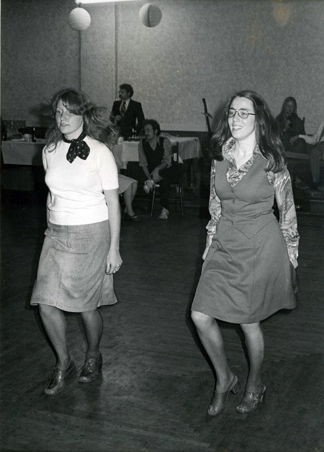 Two smartly dressed gals in dresses stepping in time together. Both look tickled to be doing their steps in front of an audience.