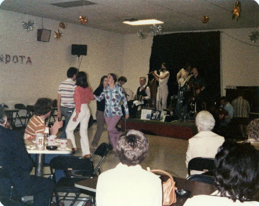 An old color picture of a room that one imagines is in a basement somewhere, drab walls, flourescent light overhead... but that doesn't stop the dancing couples or the band playing on a small stage.