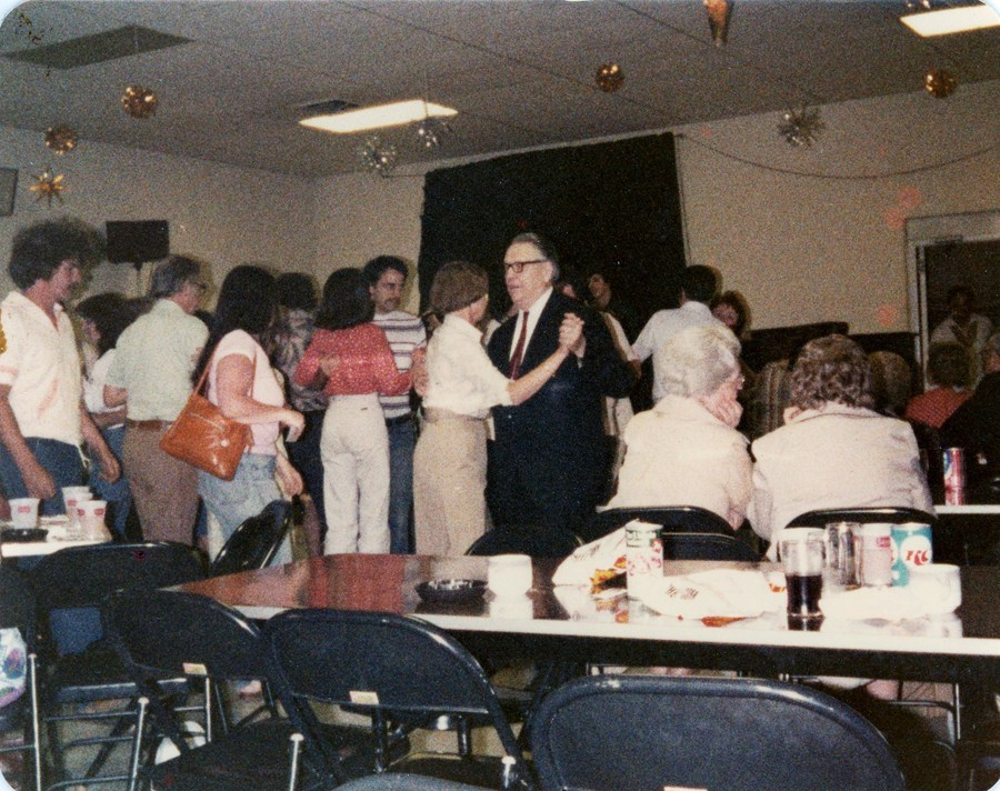 Fluffy white cakes and couple dances in a basement with folding chairs and decorations hung from the ceiling.
