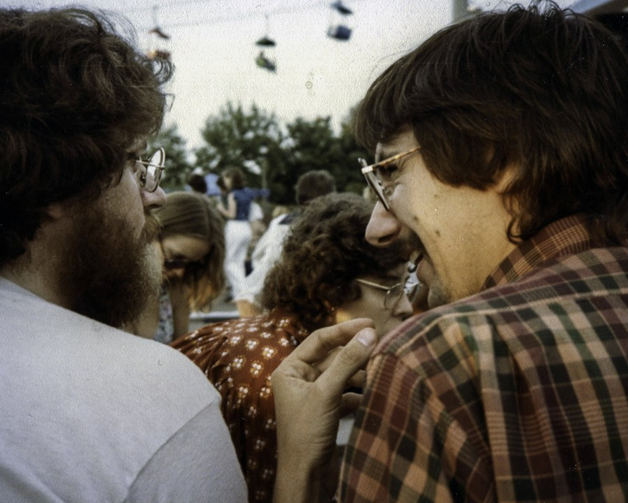 A close up of two men from behind, they appear to be sharing a joke. One, clean shaven is laughing.