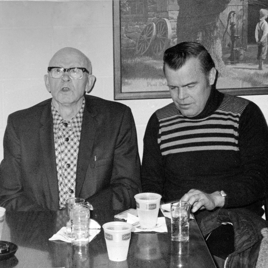 A young man and an elderly man sit at a table together. The elder man appears to be talking about something, or singing, while the younger man listens intently.