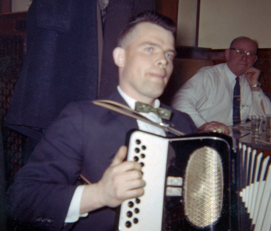Handsome young man wearing a bowtie and suit jacket plays the box. Older man looks on from the background.