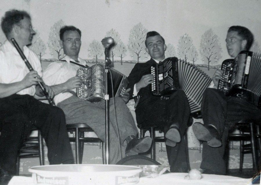 Three box players - all with one leg crossed over the other knee - hold their instruments while a fourth gesticulates to them with his flute.