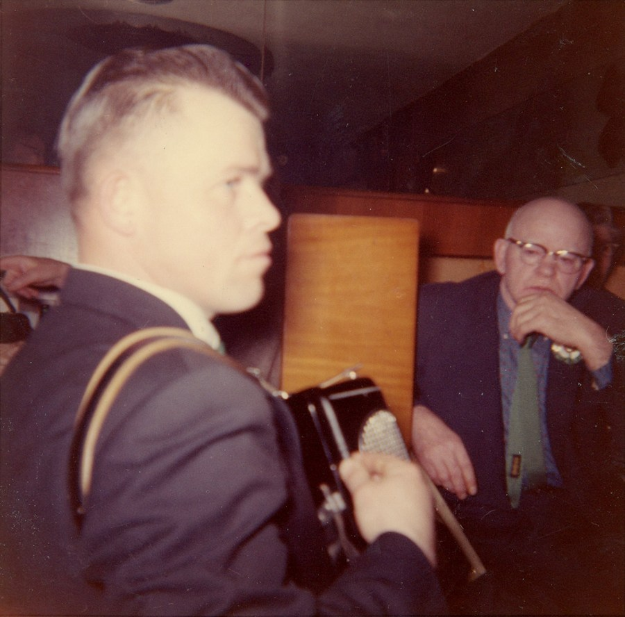 Profile of box player with older man looking on in the background.