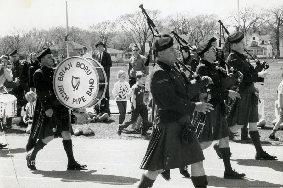 Men in kilts marching down the road while families look on. Men are playing Highland pipes. It's a sunny day that casts long shadows.