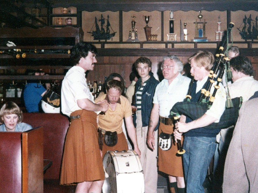 One man in a rust colored kilt stands out among a crowd of onlookers. He looks across into the eyes of a man holding a set of highland pipes which he is clearly blowing into. On the floor is a bass drum which another man is leaned over and playing.
