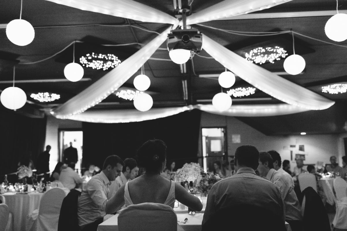 Black and white photo of a large hall with cheery swathes of white fabric draped from the ceiling, white paper lanterns hang cheerily. A crowd of fancily dressed folks eat at tables covered in white.