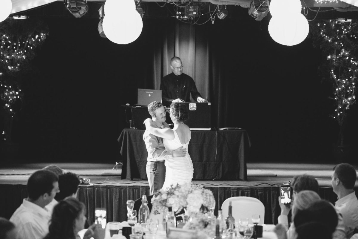 Wedding couple are having their first dance as a married couple in a lovely decorated hall. In the background a DJ stands on a stage, in the foreground, a white table is laden with crystal, goblets, wine bottles, and flowers. The couple only have eyes for each other.