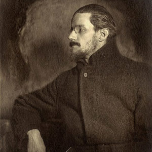 A profile of a somewhat pensive and moody looking Joyce in a dark overcoat.