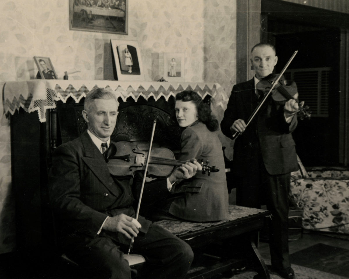 An old black and white photo of three musicians in a house, one woman on a piano bench facing the keys, two gentlemen pose on either side of her, both hold fiddles and bows in their hands. The room is well appointed with wall paper, a lace table cloth tops the upright piano. The three musicians are all well dressed in dark suits.  The lady's dark hair is pulled back neatly and stylishly.