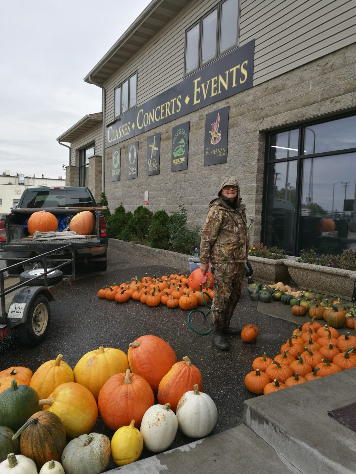 Pumpkin Jack stands proudly, though covered head to toe in camouflage, in front of the TCJ building with his pickup truck and trailer in the background. Surrounding him are piles of prodigious pumpkins. Pumpkins of various colors and shapes which he has just paused from washing. He looks delighted.