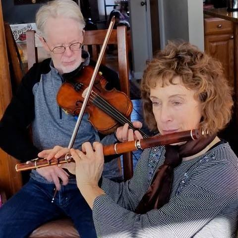 Dave and Suzanne Rhees holding fiddle and flute.